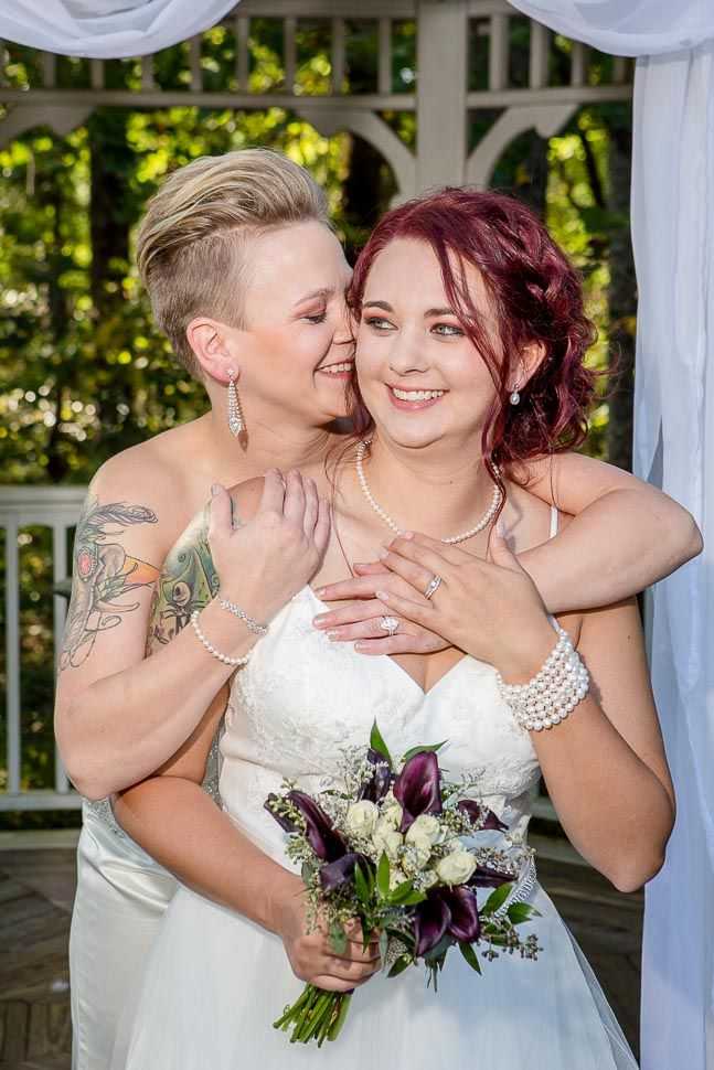 Two brides in white wedding dresses sharing a tender moment and laughing after just being married.