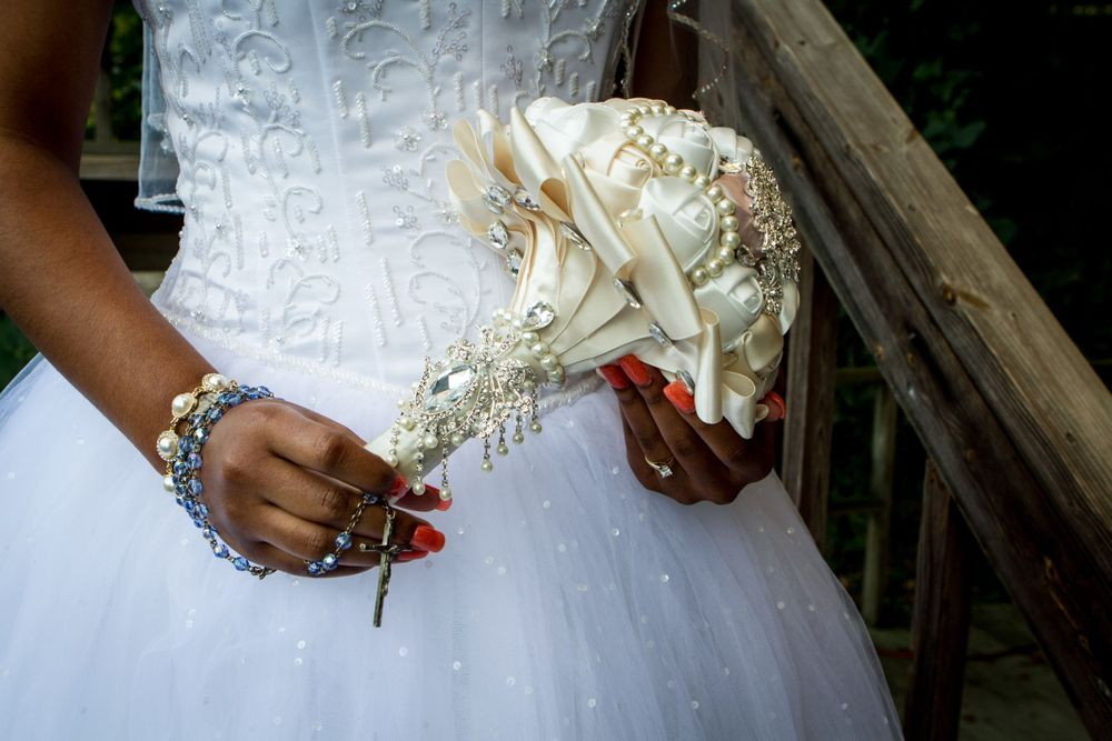 Closeup picture of a bride holding her bouquet with a rosary beads accent