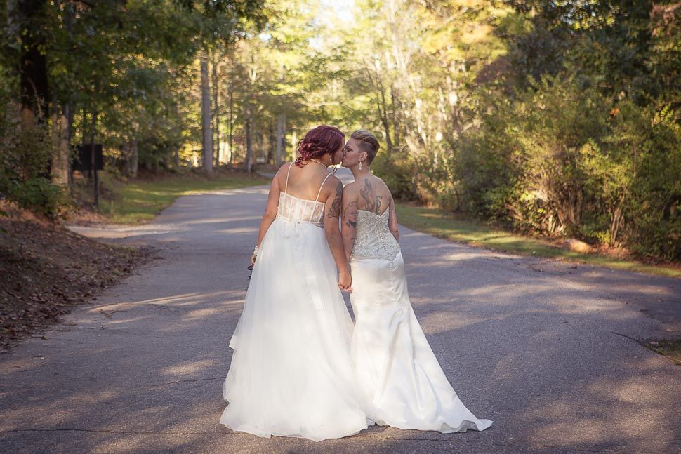 Brides in white wedding dresses kissing as they leave their wedding and head to Happily Ever After
