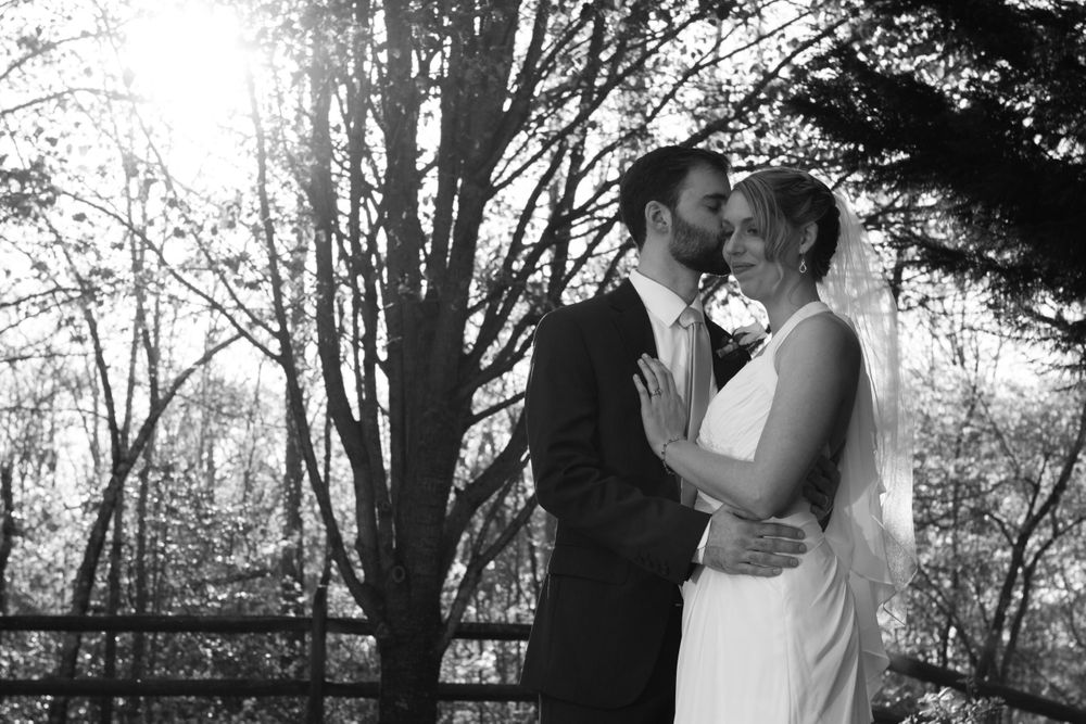 Black & White outdoor picture of newlyweds kissing under tress with the sun behind them.