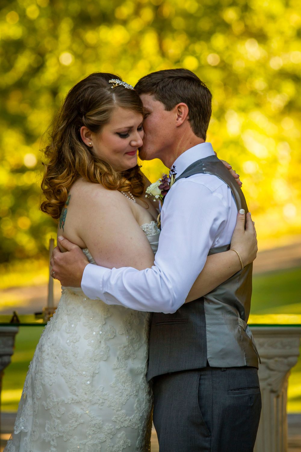 A newlywed couple hug at their outdoor wedding