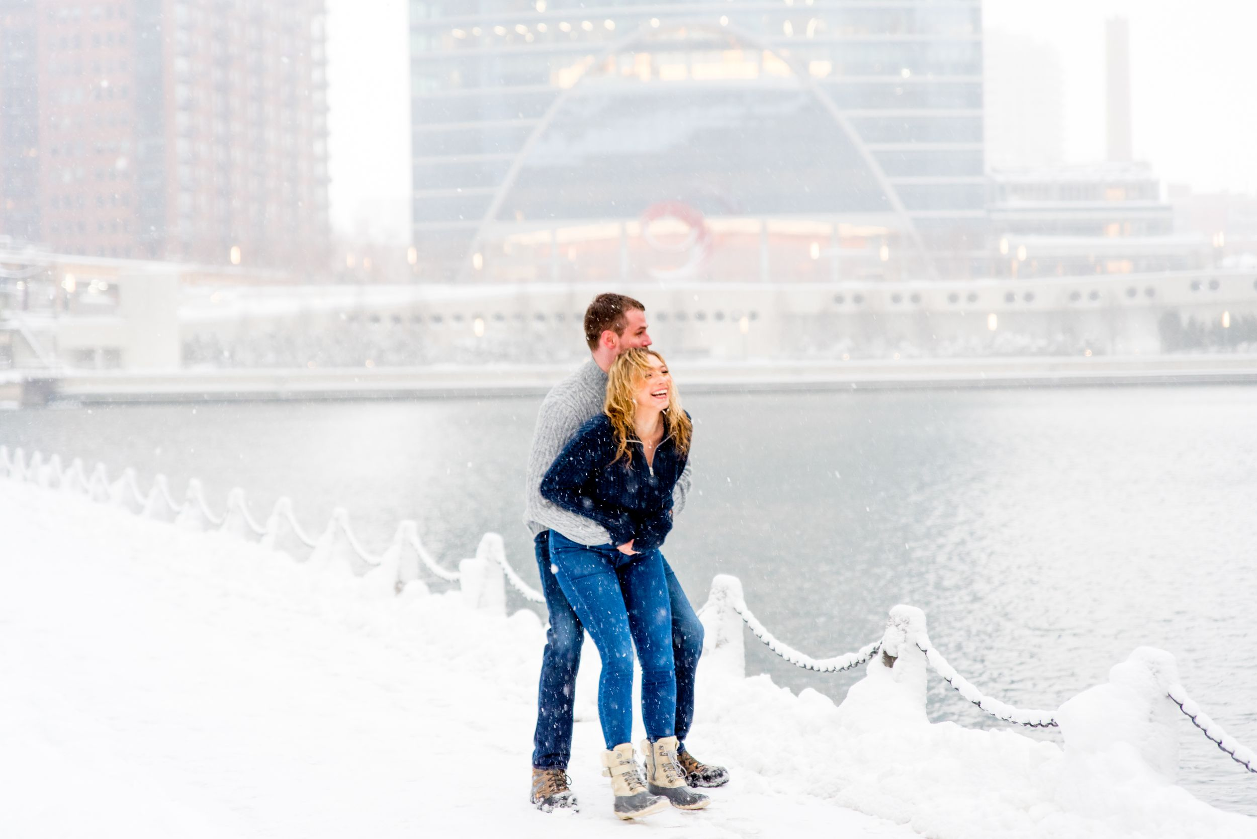 man and woman in navy and grey sweaters smiling in snow at Merchandise Mart