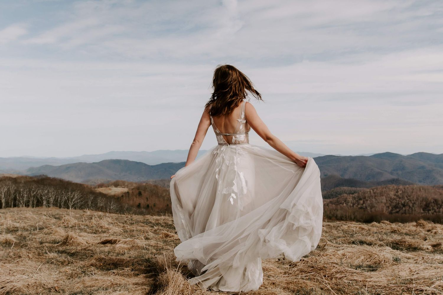 Woman twirling in her wedding dress on top of a mountain at sunset during her Asheville elopement
