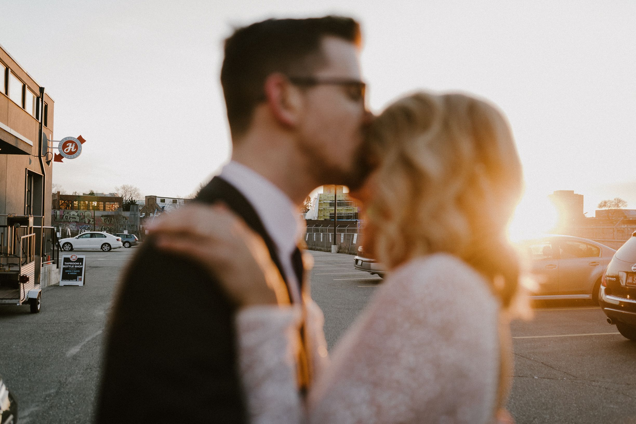 Blurry image of groom kissing bride`s forehead at the Drake Commissary Toronto at golden hour.