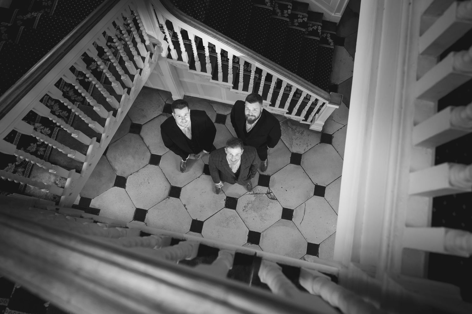 Groomsmen looking up through a stairwell