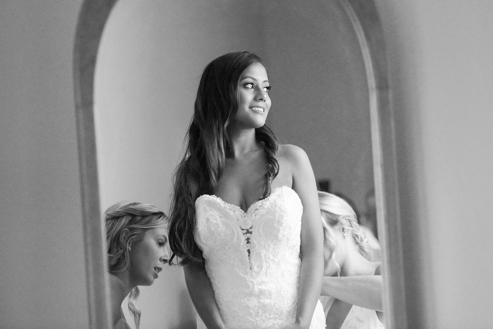 bride's reflection in mirror while girls button her dress