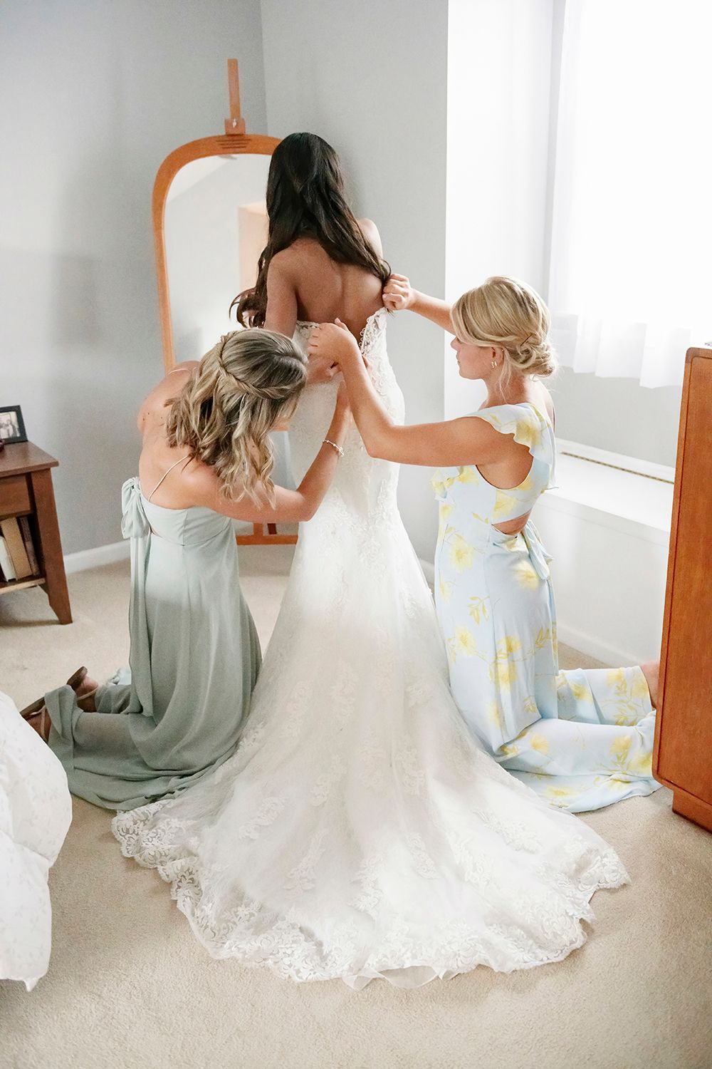 girls buttoning the bride's dress