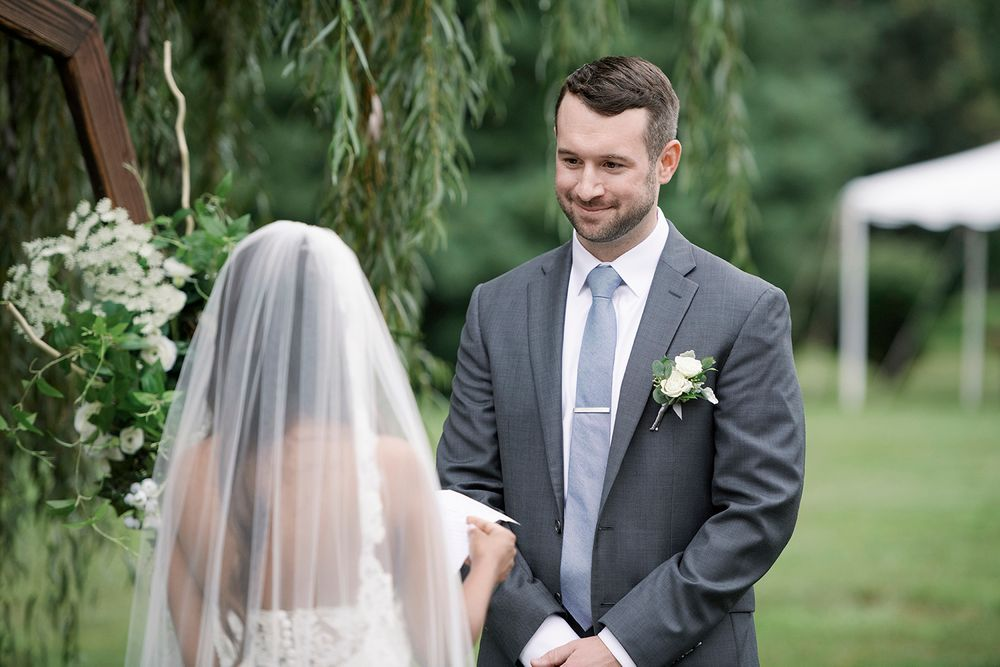 groom listens to bride reading her wedding vows during the ceremony