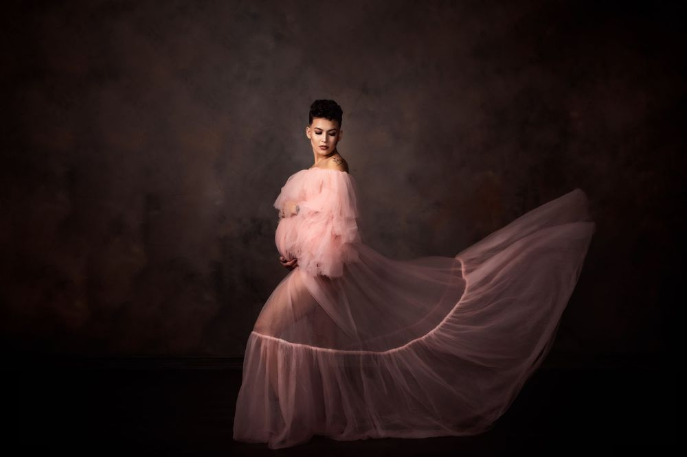 Beautiful Maternity Portrait taken in studio of a mama in a flowing pink maternity dress.