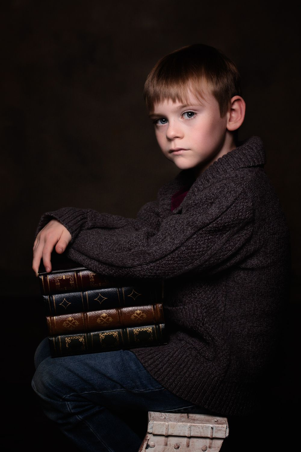 Fine Art child portrait of a young boy holding a stack of fake books.