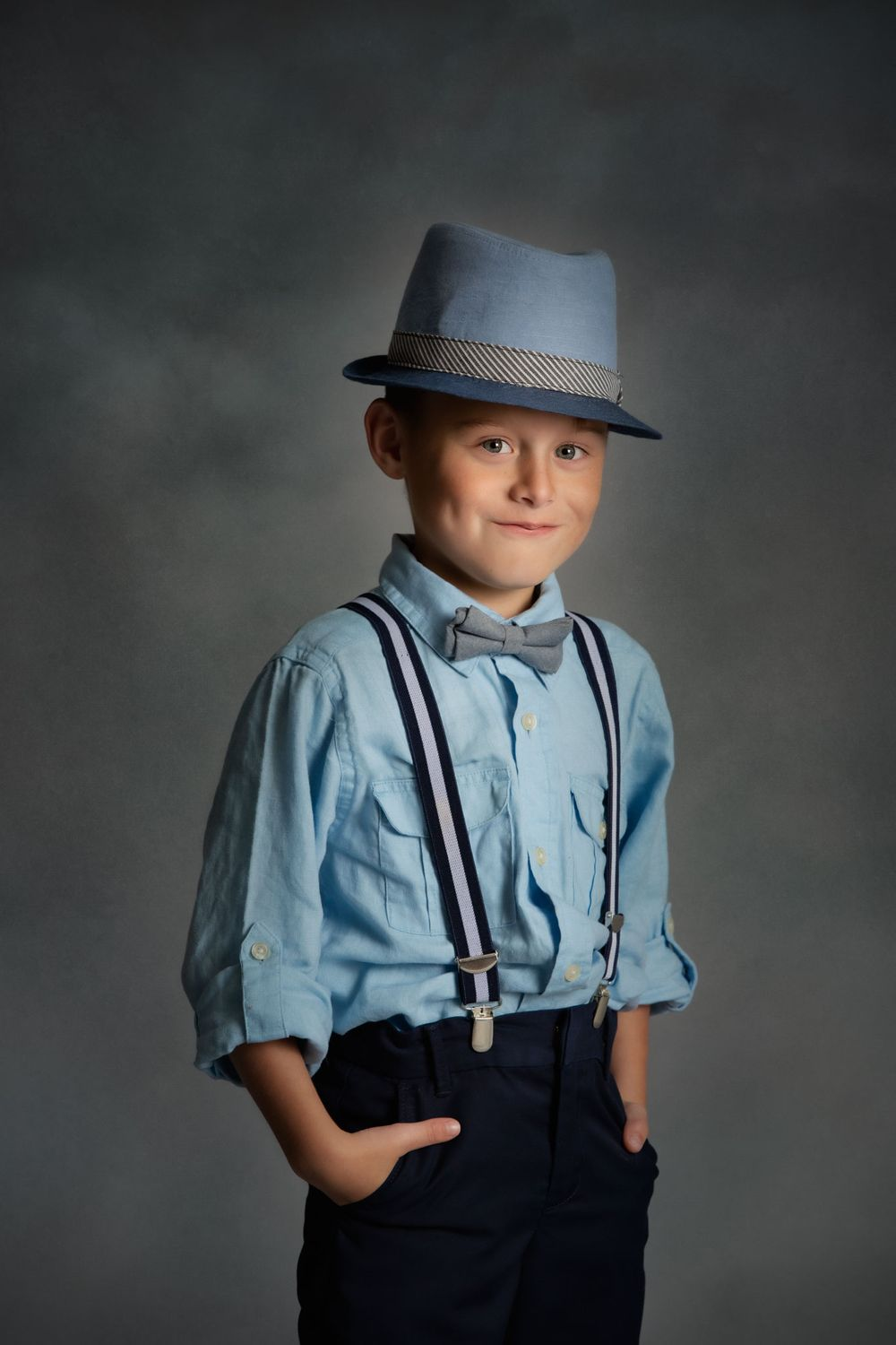 Fine Art portrait of boy with suspenders and bow-tie.
