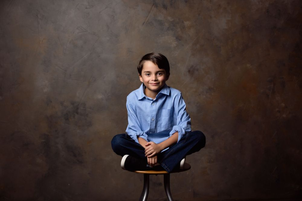 Child portrait of young boy sitting on a stool.