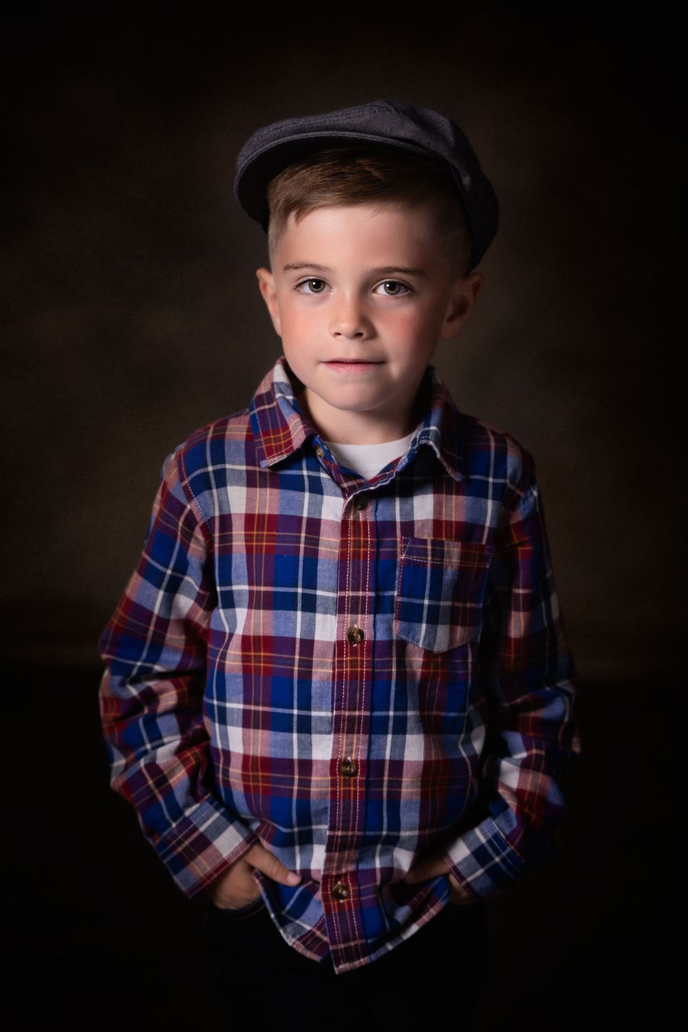 Fine art portrait of young boy wearing a flannel shirt and newsboy cap.