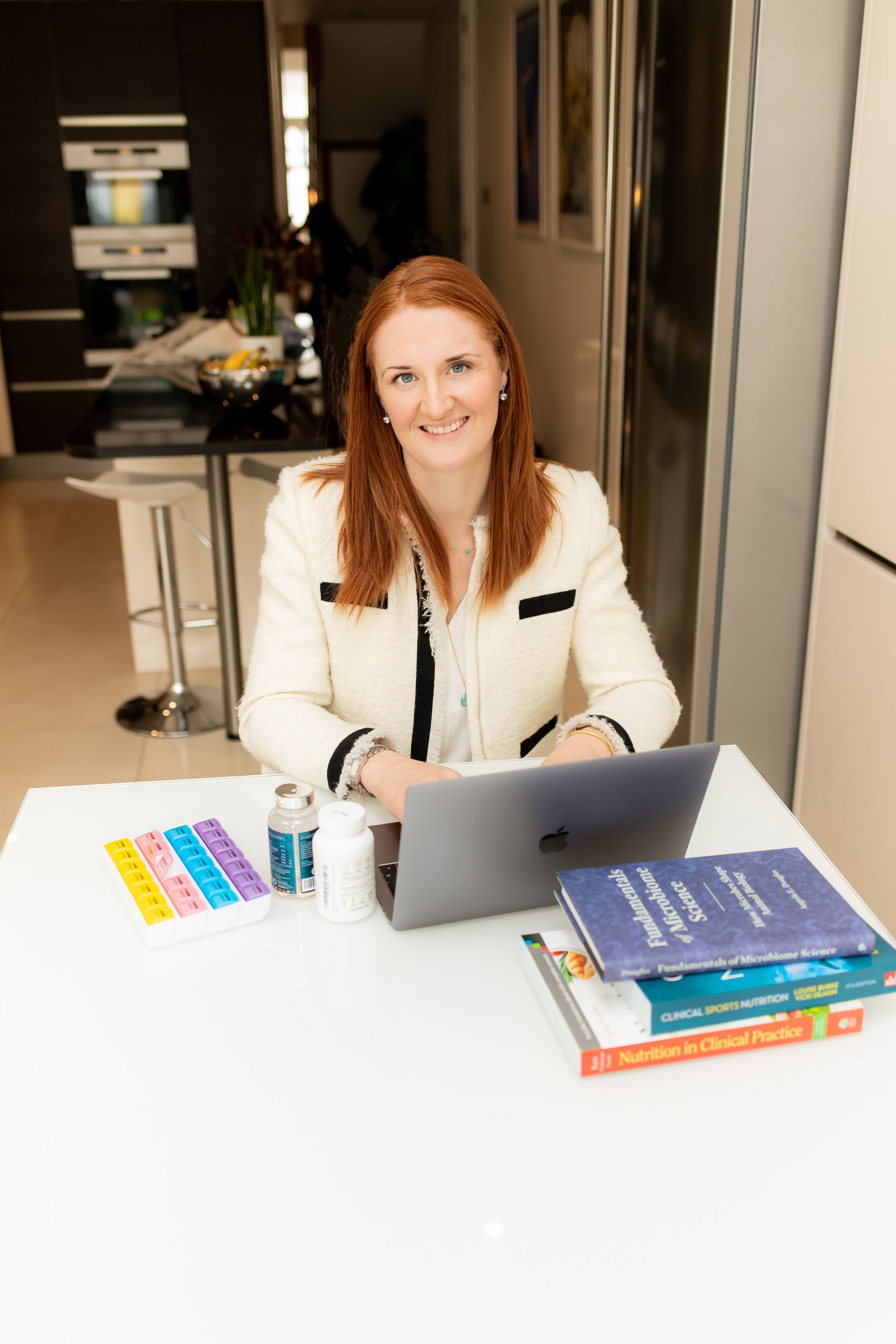 Nutritionalist sits at her table with her laptop, supplements and reference books - Corporate Photography