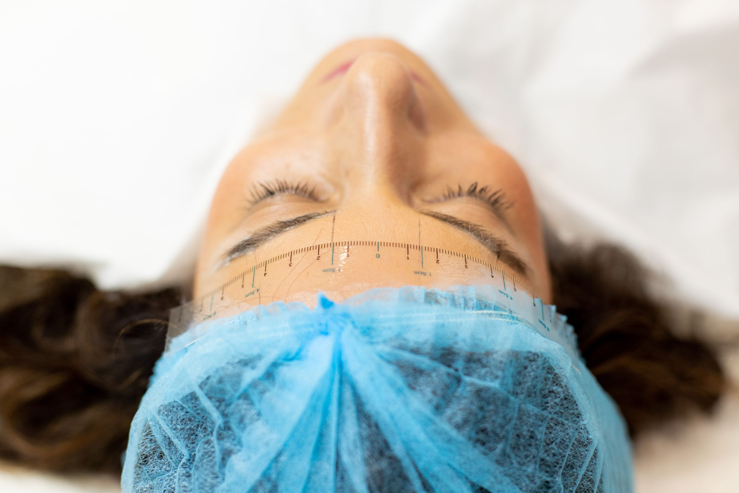 Close up image of a lady waiting to hoverer eyebrows treated wearing hairnet - Corporate Photography