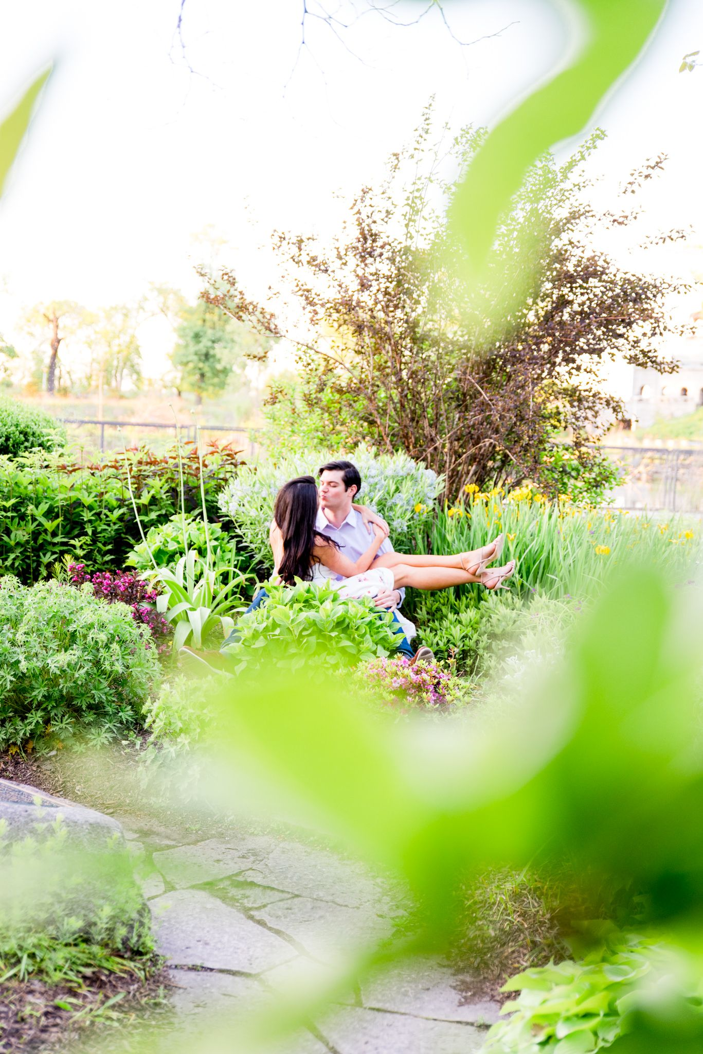 woman sitting on fiance's lap in Lincoln Park as they kiss for engagement pictures in the garden