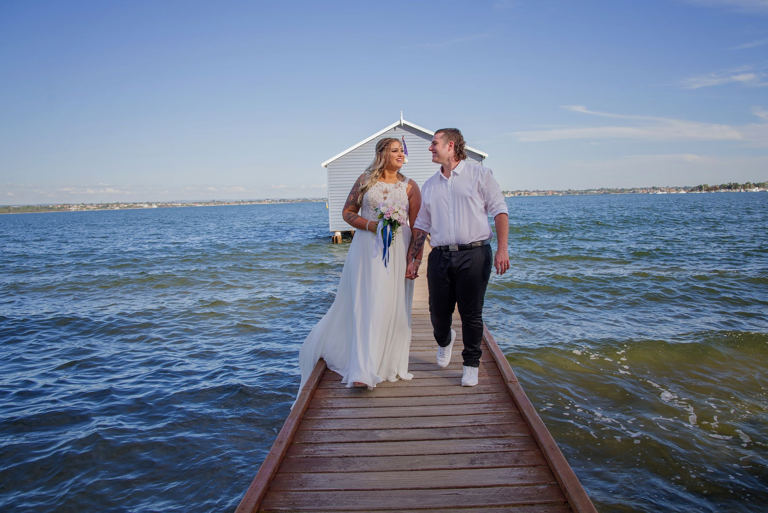 bride and groom walking on bridge and smiling at each other blue boat house behind them