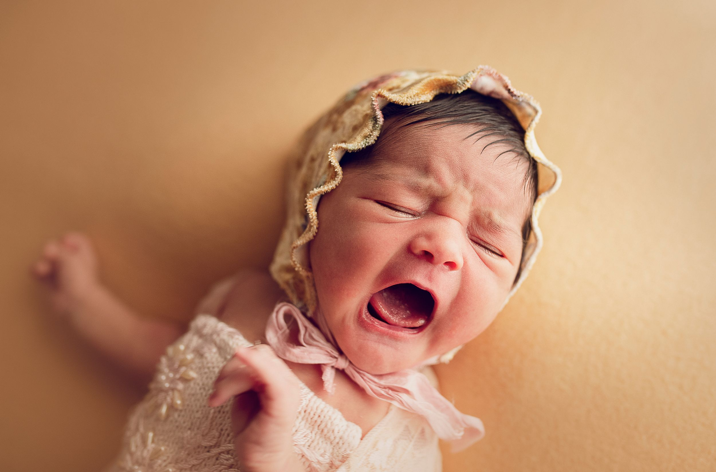 newborn baby wearing a bonnet crying peach backdrop