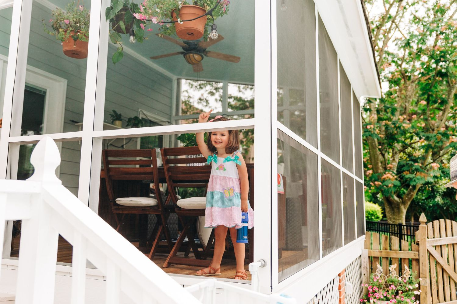 Preschooler playing on porch for backyard family photography session in Charlotte, NC