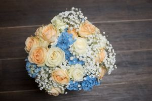 Brides white roses bouquet on a rustic wood floor at Mansfield Manor in Nottingham