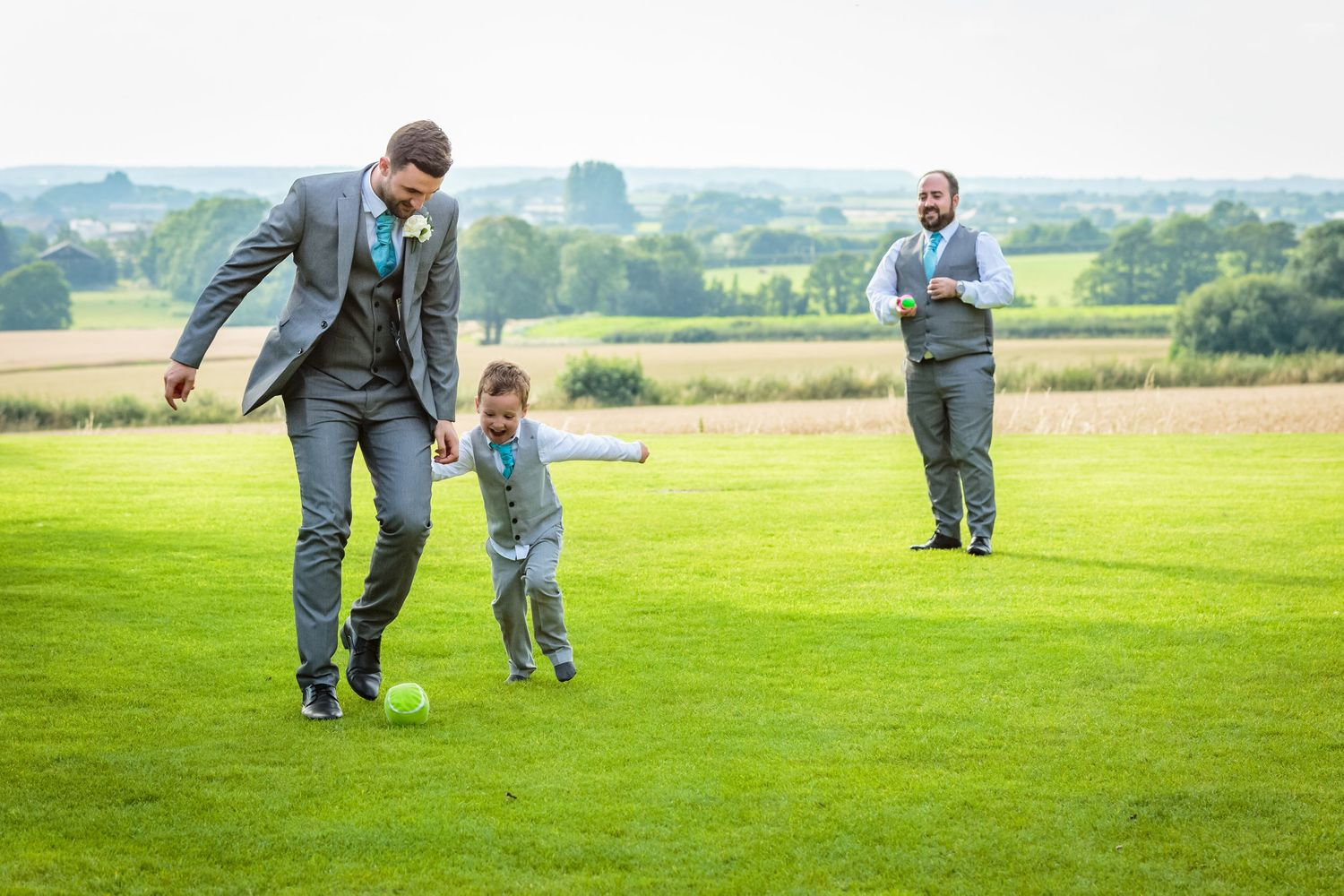 pageboy playing football with the best man tries to get the ball off him