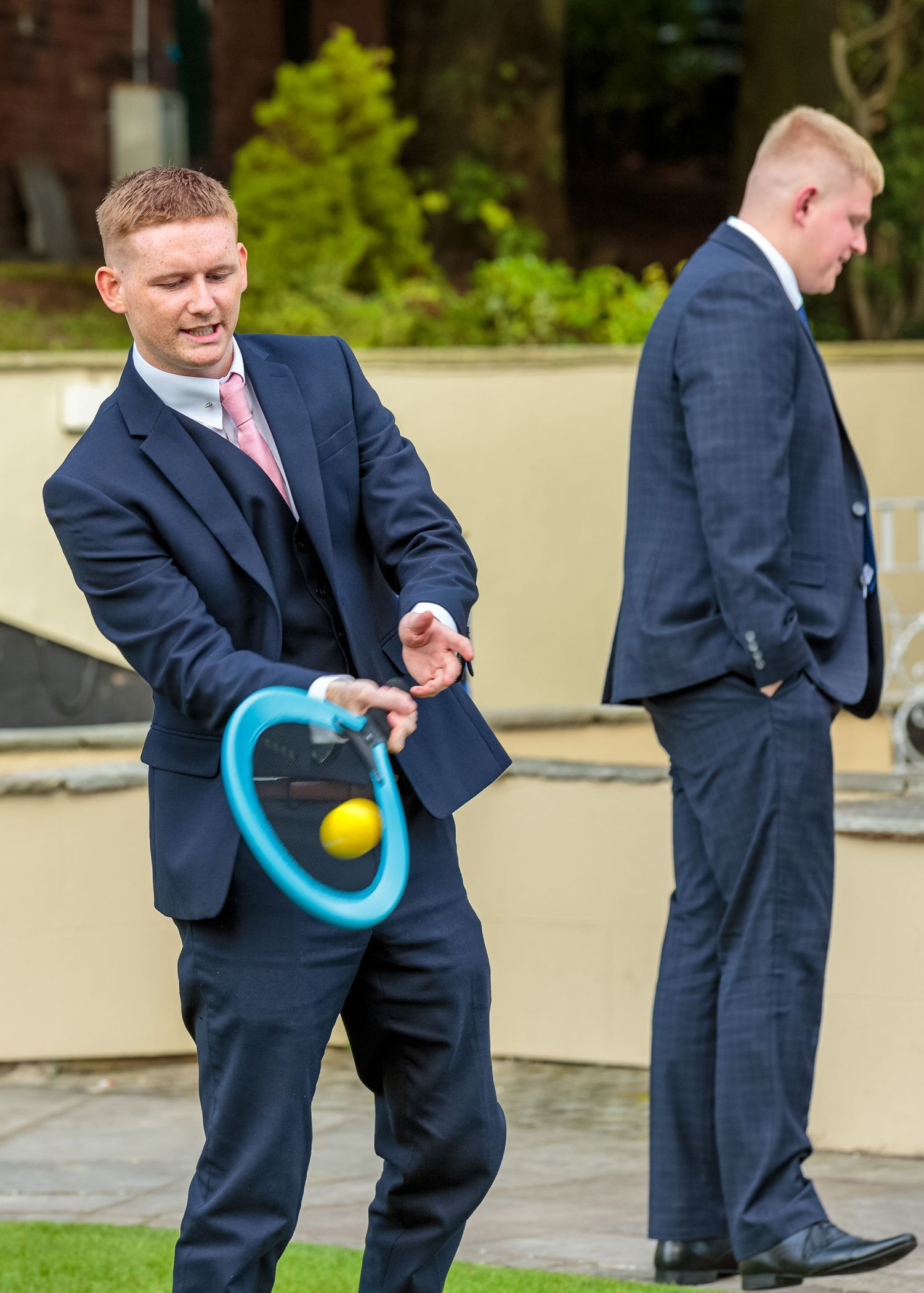 wedding guest in a smart suits hits the ball while playing tennis