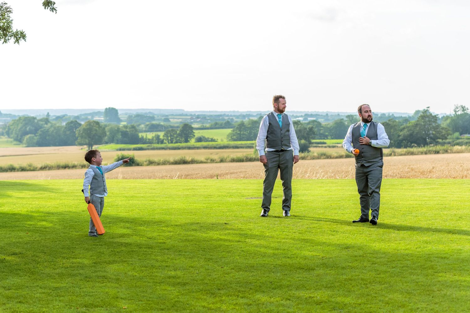 pageboy holding a cricket bat points to show the ushers where he hit the ball