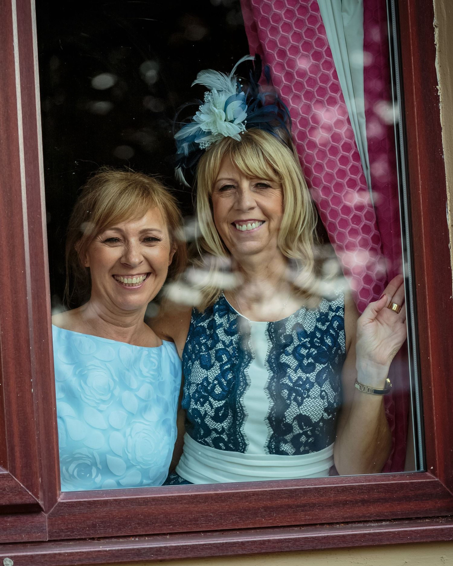 grooms mum and her friend smiling looking through their room window