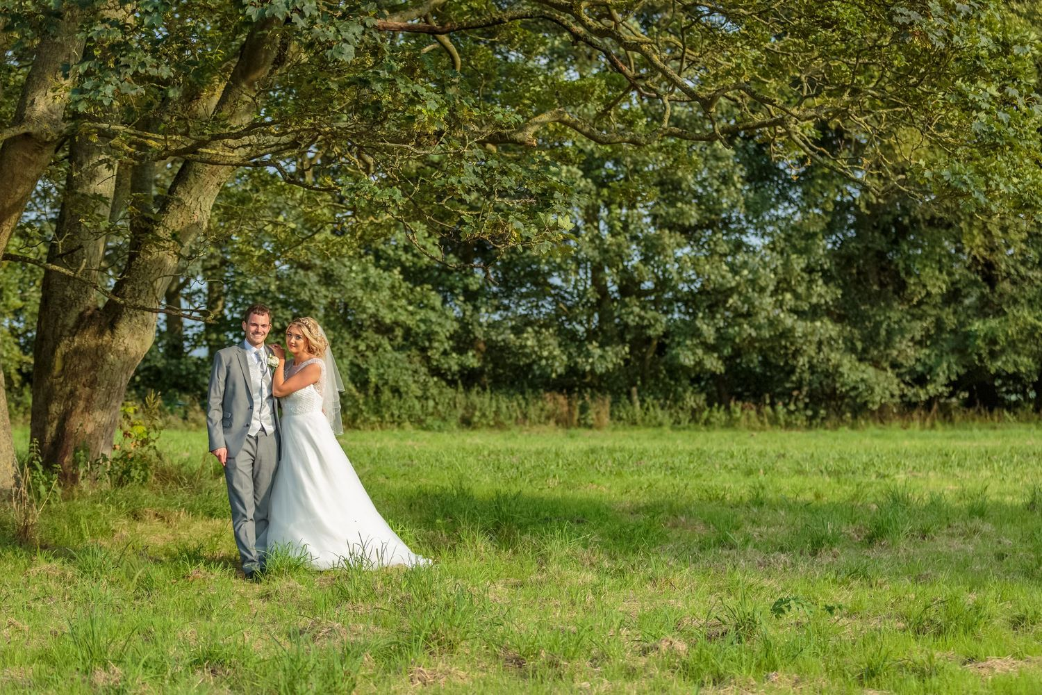 bride and groom posed her hands on his shoulder under a tree in the country grounds at west tower
