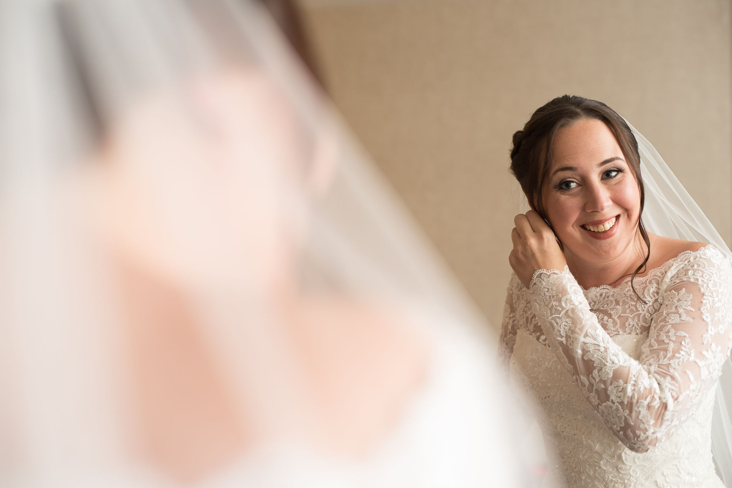 happy bride in long sleeve lace gown and veil looking in mirror while putting on earrings | NJ Wedding Photographer
