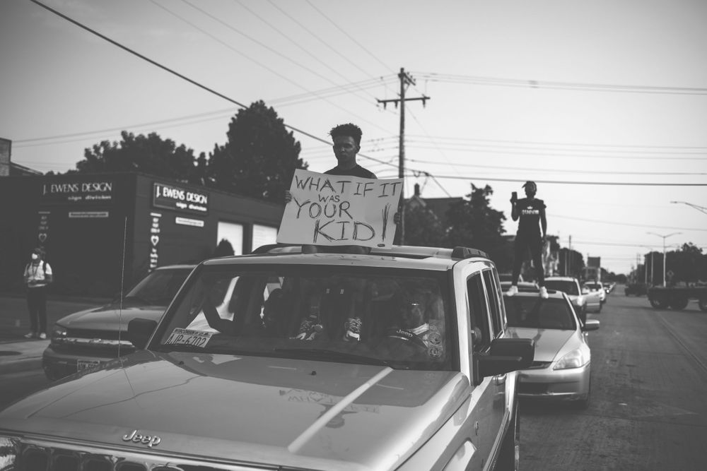 "A man sits out of the sunroof of a car holding a sign that reads, ""What if it was your kid!"""