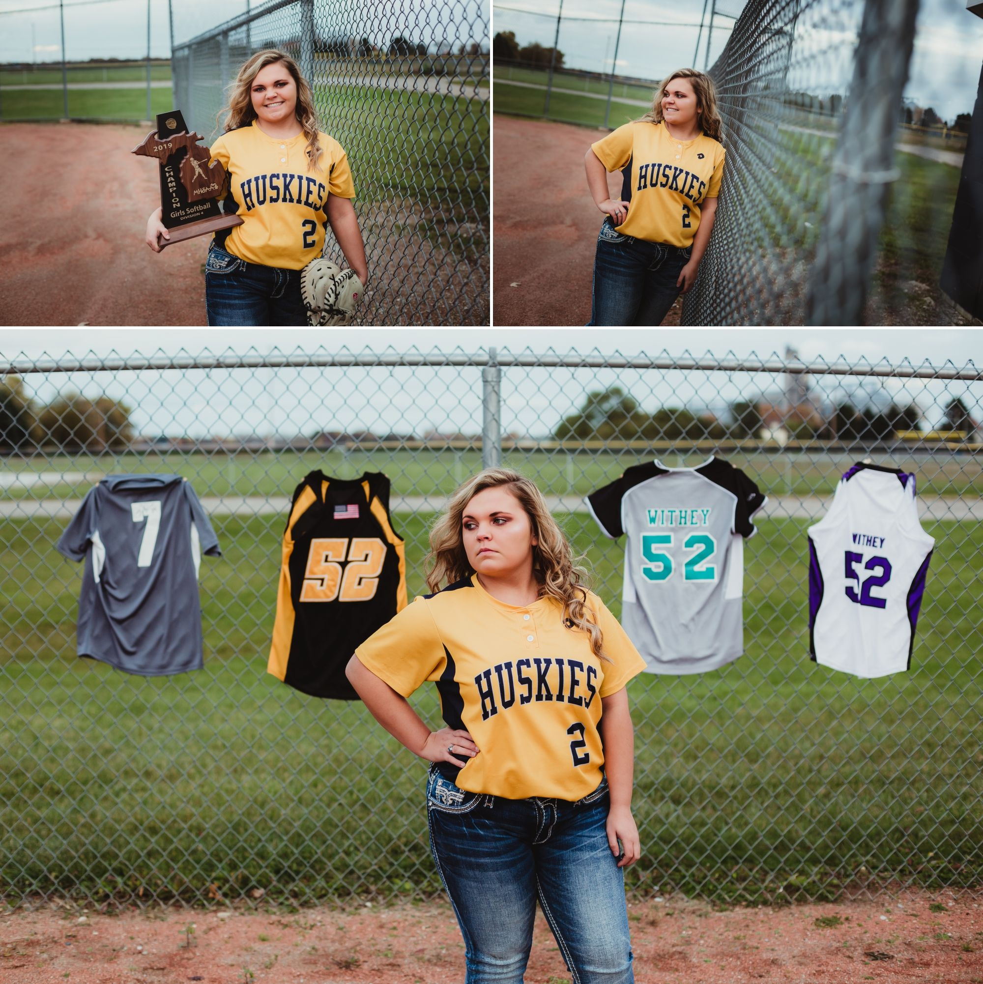 High school senior girl near the fence on a softball field with a trophy and jerseys displayed.