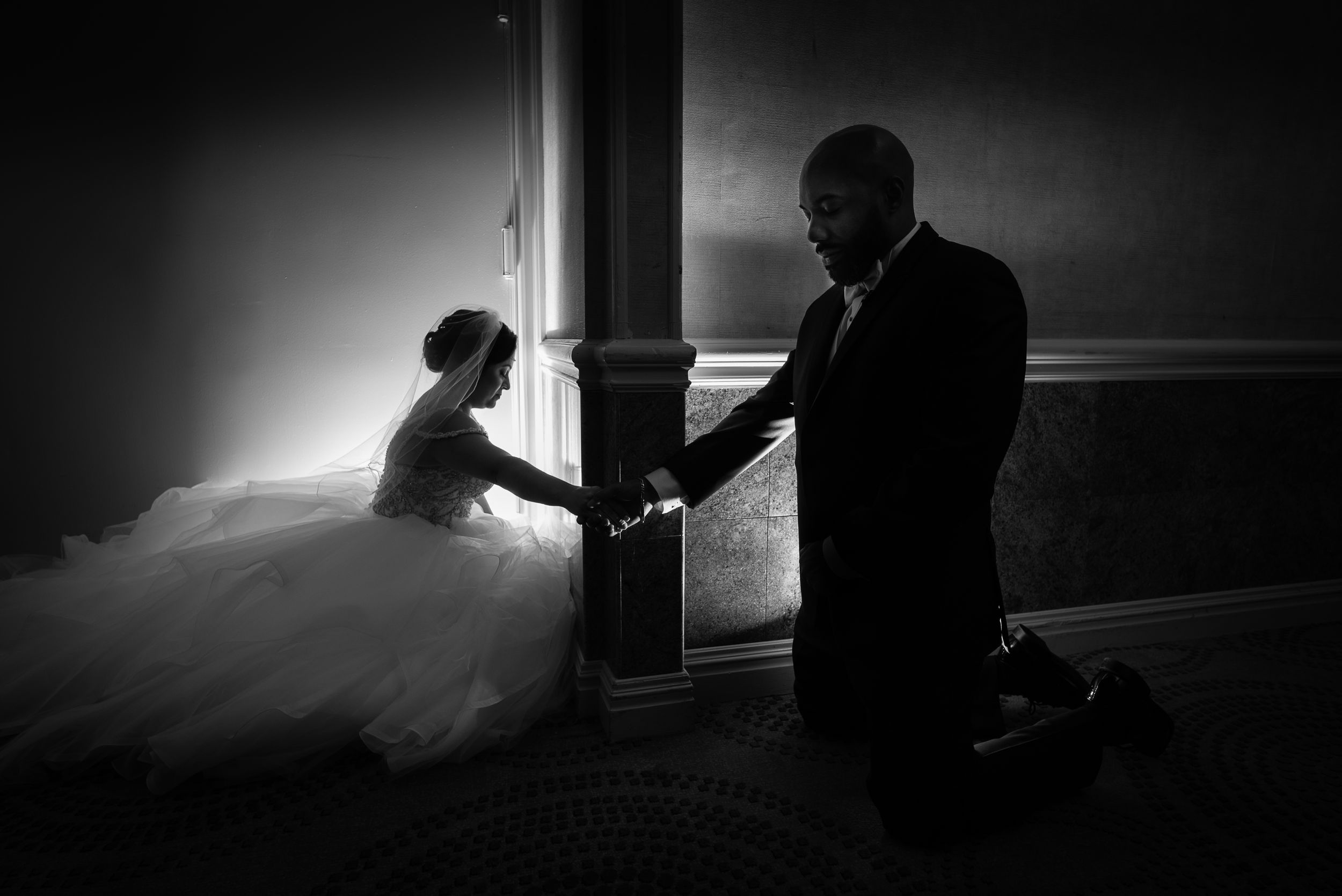 black and white photo of couple praying before ceremony separated by a wall | emotional wedding photography nj