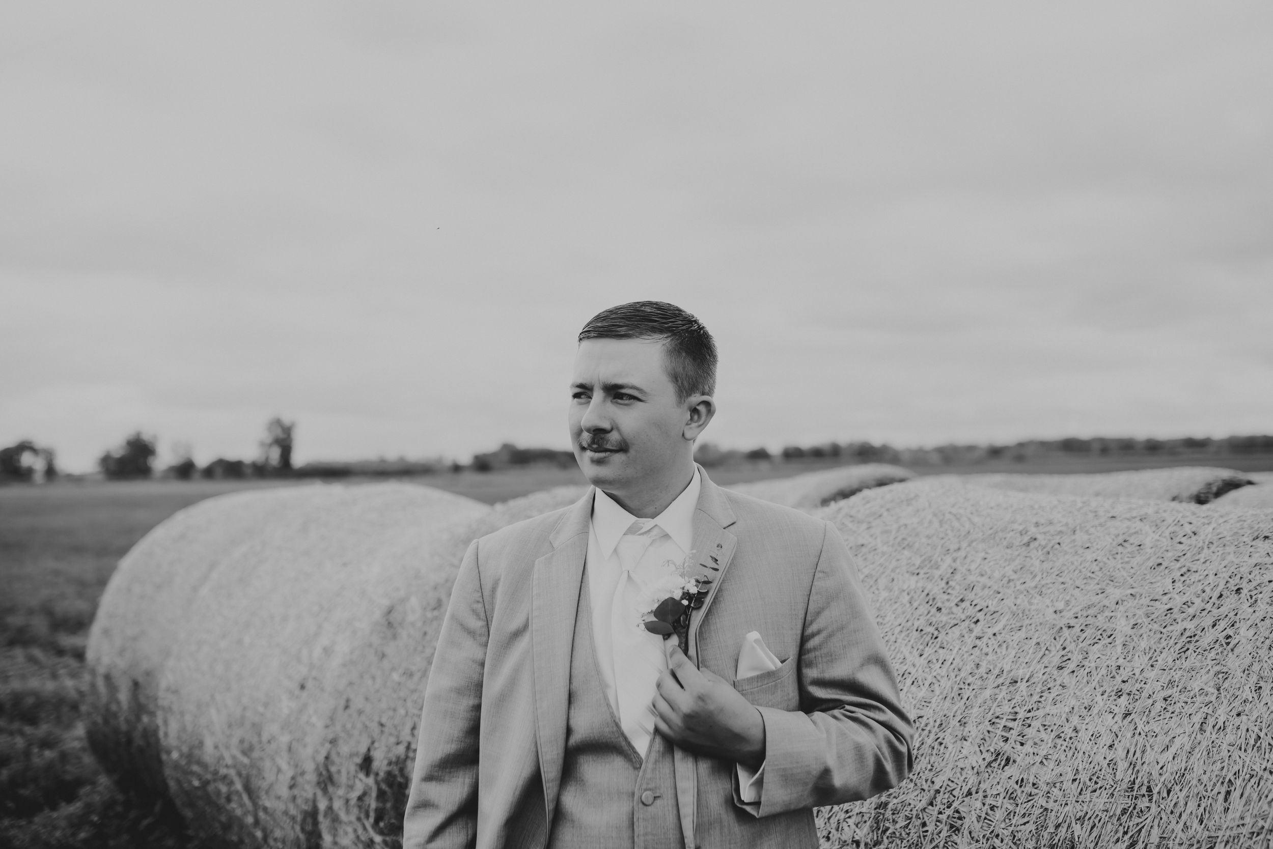 Black and white photo of groom looking off to his right while holding his jacket.