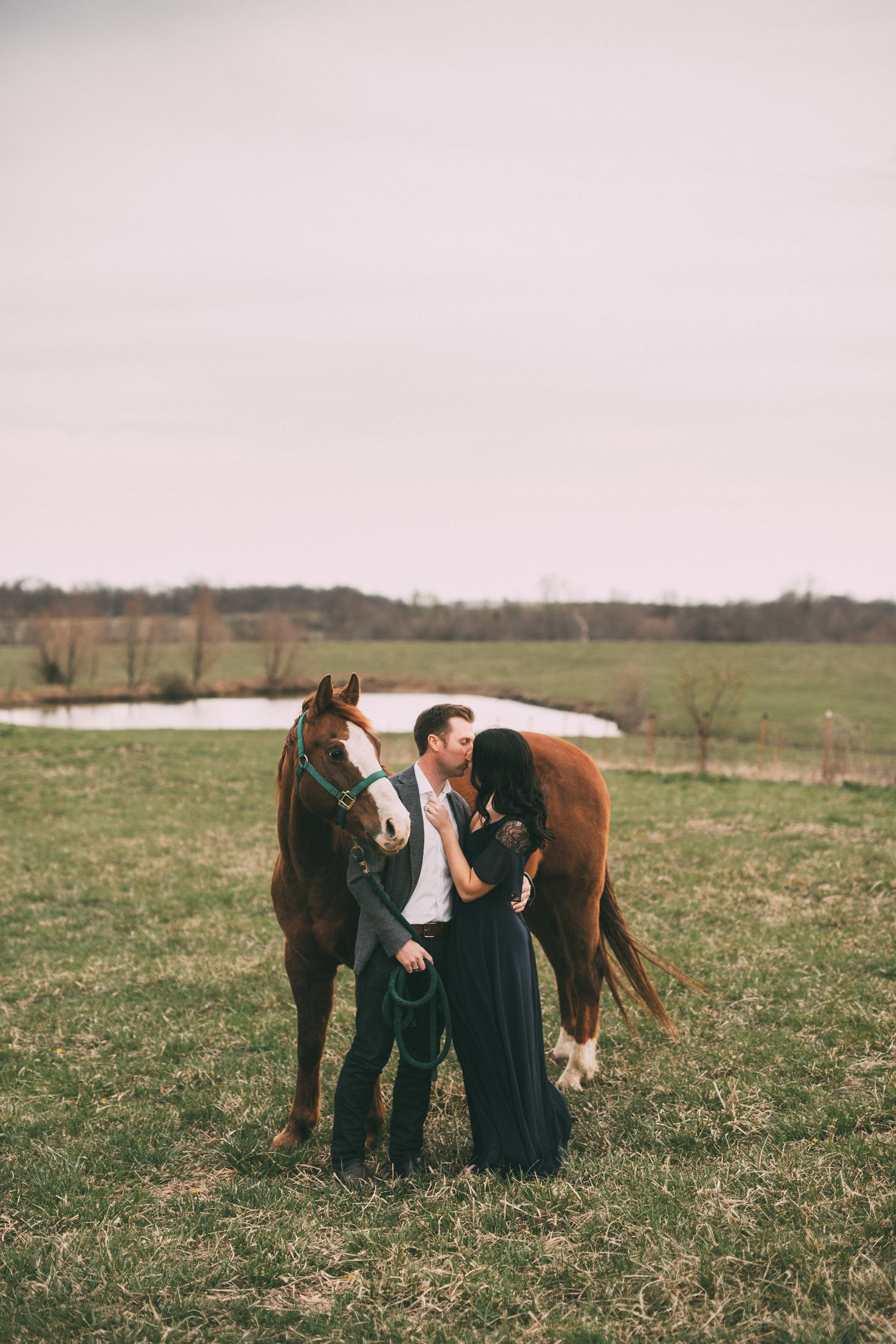 Couple kissing beside their horse in front of a pond and a field