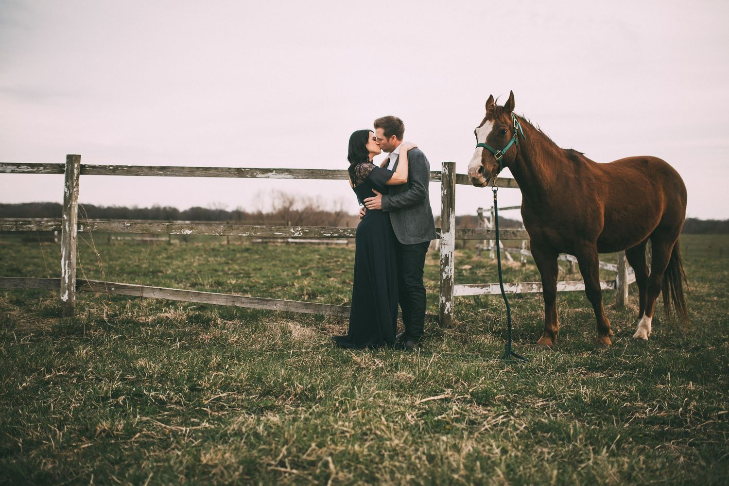 couple kissing by their horse in front of an old fence in the country