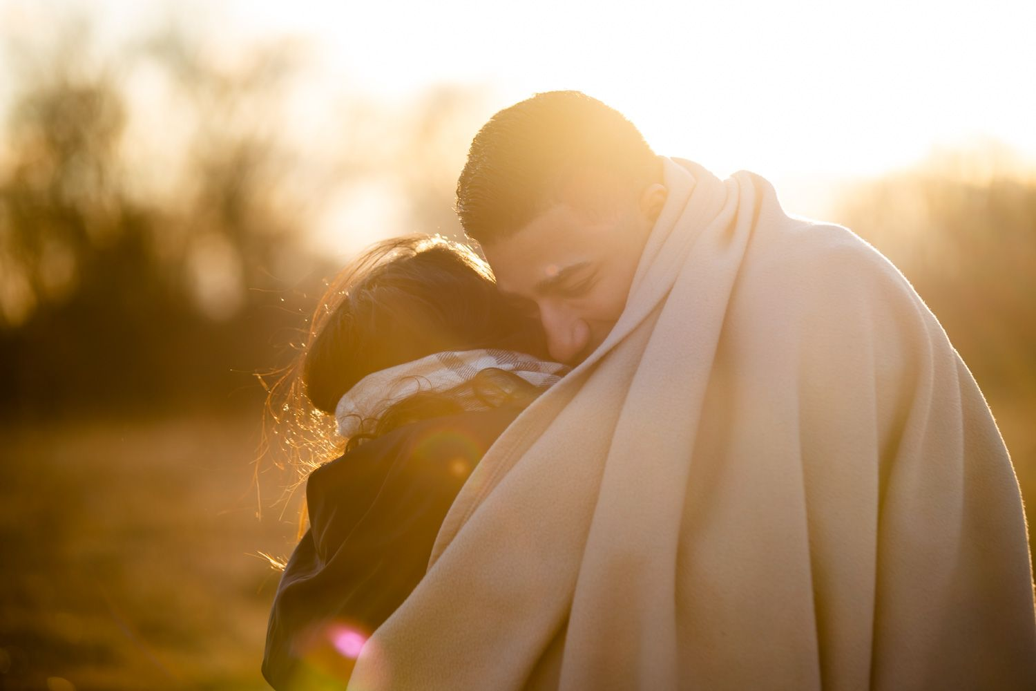 Engaged couple hug in the golden hour sunset in Hudson Valley, New York