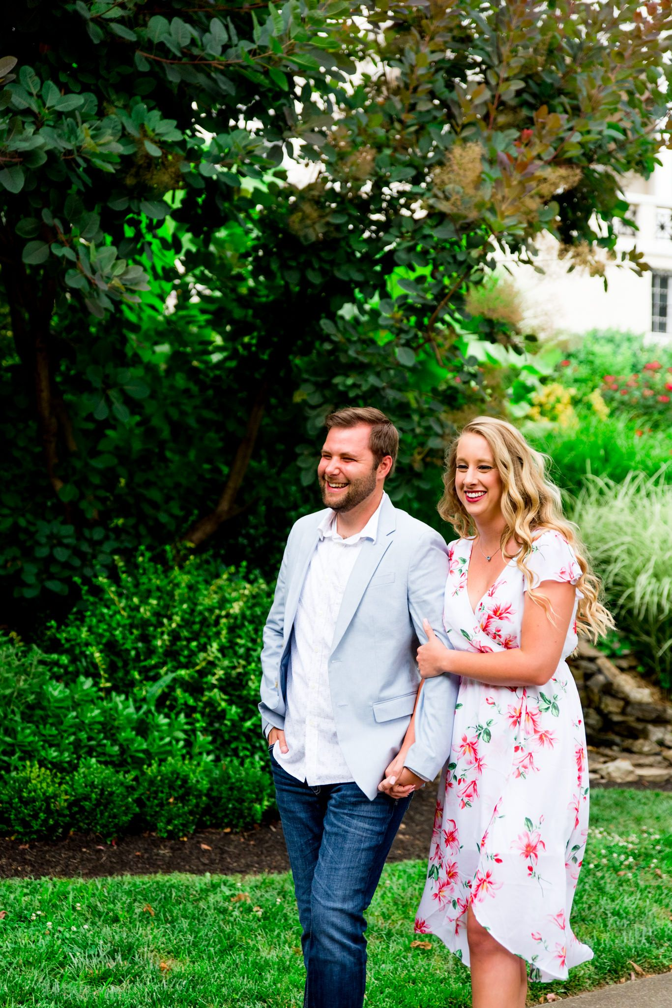 engaged couples in floral dress and light blue suit jacket and jeans walking in rainy Louisville and laughing