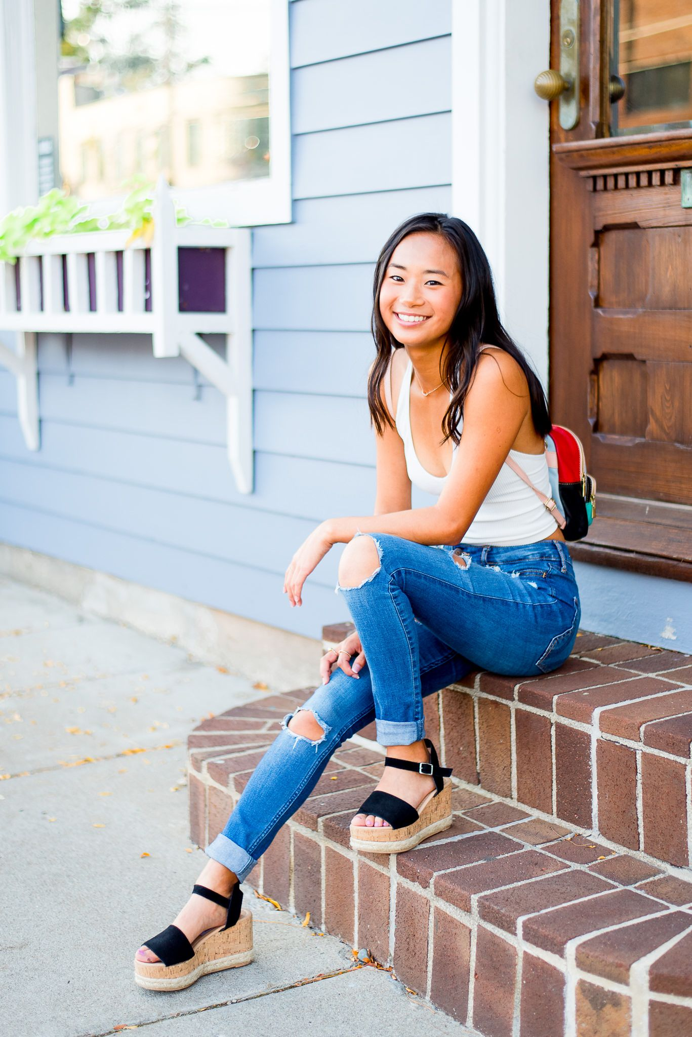 high school senior girl sitting on a stoop in downtown Cincinnati