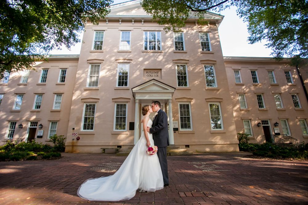 Groom Mike and bride Kelsey kiss on USC's Horseshoe in front of Rutledge Chapel in Columbia, SC.
