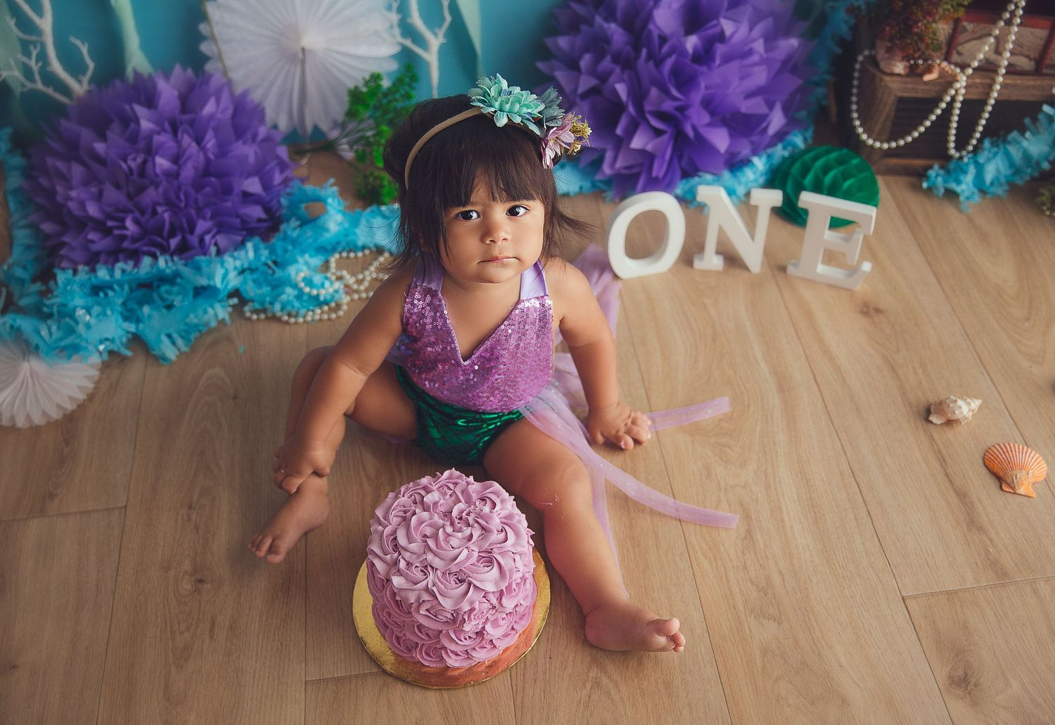 baby girl looking at the camera with pink cake