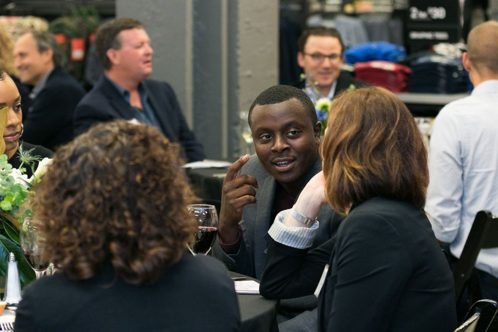 Attendees conversing at the table during the event inside of the Nike store.