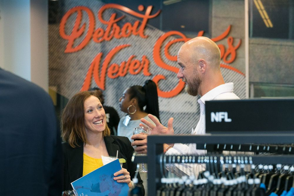 Attendees conversing before the event begins inside of the Nike store with Detroit Never Stops artwork in the background