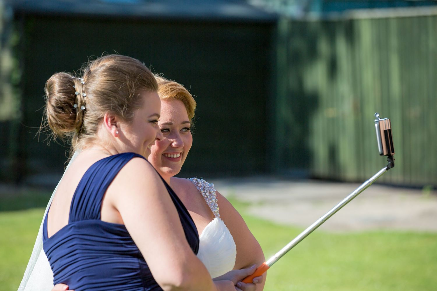 Bride and Bridesmaid use a selfie stick to take a photo on a phone at Briars Hall Wedding Venue Burscough near Ormskirk