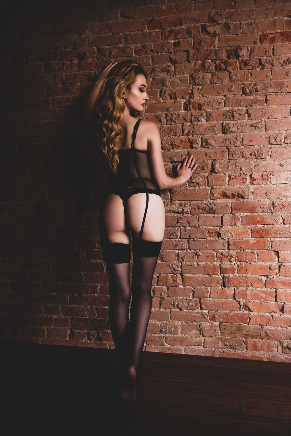 BLONDE CHICK IN BLACK LINGERIE LEANING AGAINST A BRICK WALL LOOKING OVER HER SHOULDER AS HER LONG HAIR TUMBLES DOWN