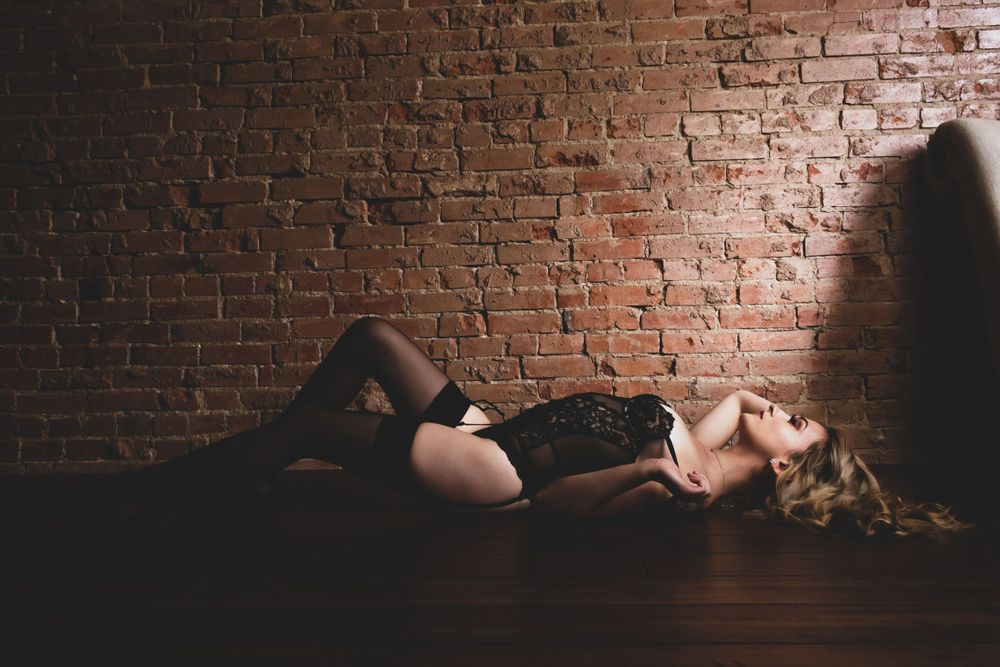 ON HER BACK, LYING ON THE FLOOR WITH HER BLONDE LOCKS SPRAWLED OUT