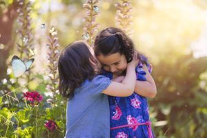 2 sisters having a sweet moment in their family photo session in the grounds of The Old Cheese Factory in Berwick.