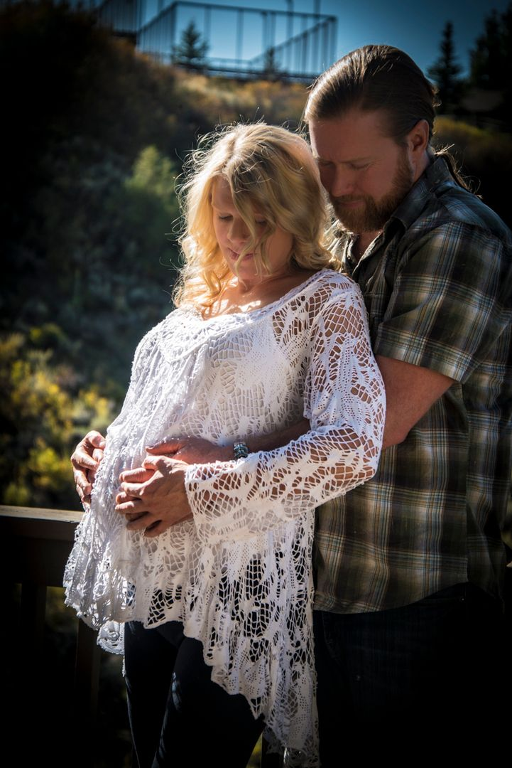 Maternity photo with woman in lace and man in plaid wrapping his arms around her