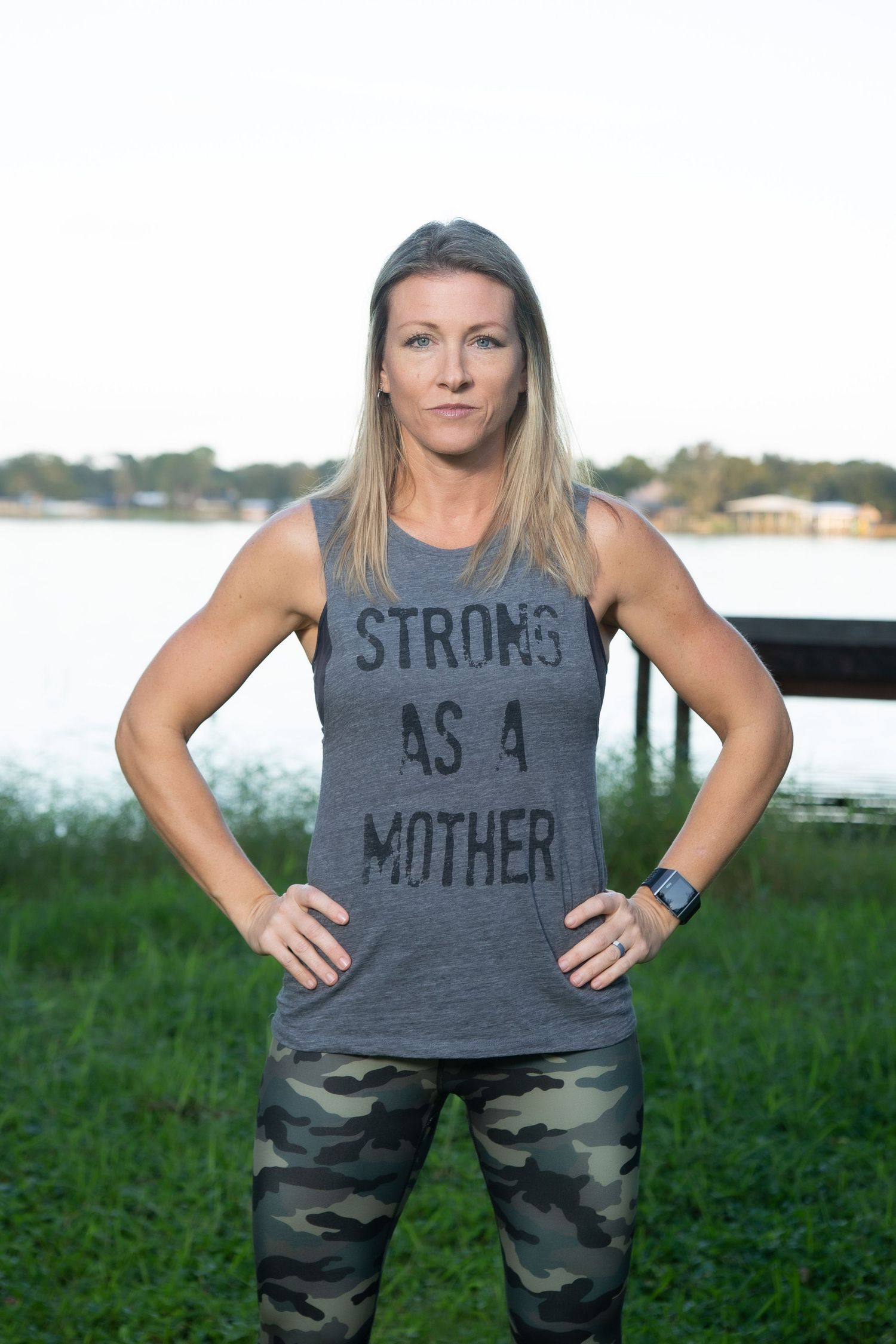 female fitness instructor standing in power pose in front of a lake