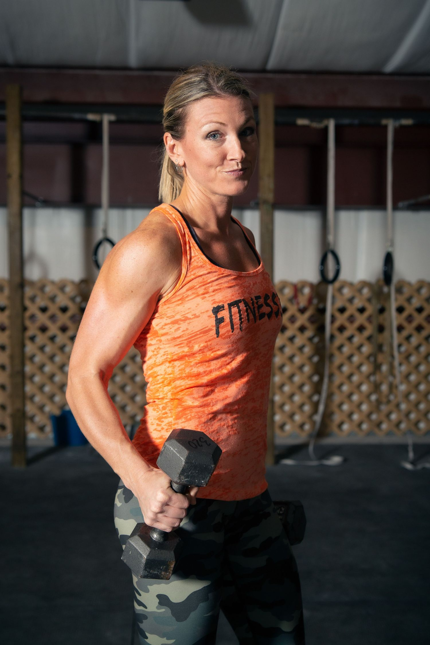 female fitness instructor posing with weights in gym